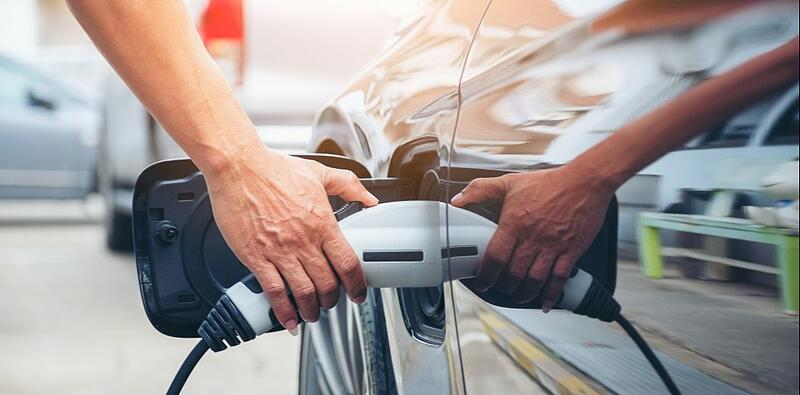 hand-hold-of-charging-modern-electric-car-battery-on-the-street-which-are-the-future-of-the_t20_98XkZO (1)