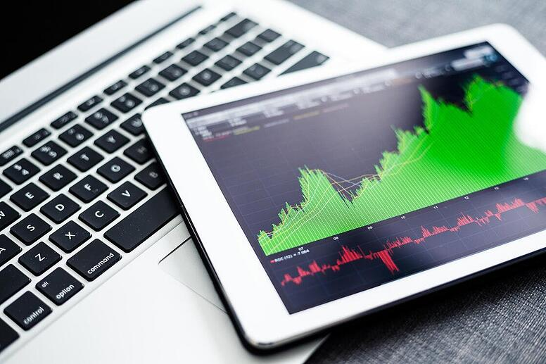 stock-market-graphs-on-tablet-pc-with-laptop-compu-NYNNAH4